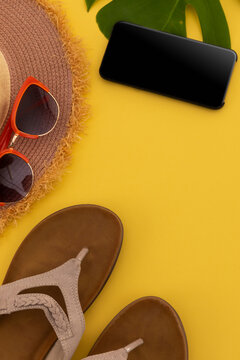 Sunglasses, flip flops, sunhat and smartphone on yellow background