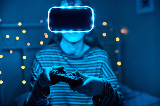 Teenage Girl Playing Video Game At Home In Bedroom Wearing Virtual Reality Headset At Night