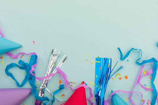 Party hat, party blowers and confetti on blue background