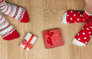Christmas red socks on wooden floor. Two pairs of feet, dressed in Xmas socks, stand near presents. Concept of happy family at home