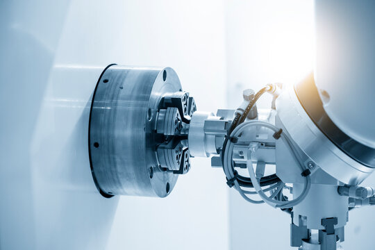 The robotics arm gripping the metal part from CNC lathe machine. The hi-technology  autonomous manufacturing process of automotive parts by turning machine.