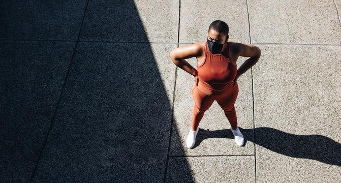 Plus size woman taking break from workout outdoors