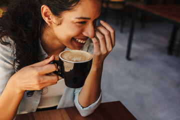 Happy woman holding cup of coffee and smiling