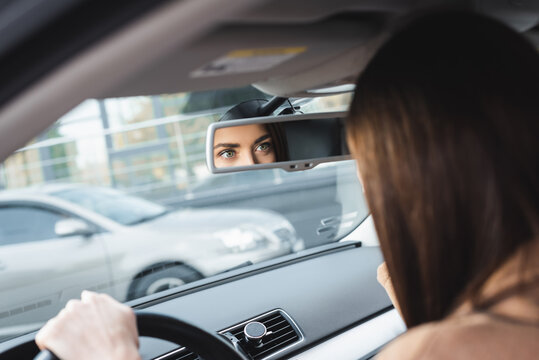 woman driving car and looking in rearview mirror on blurred