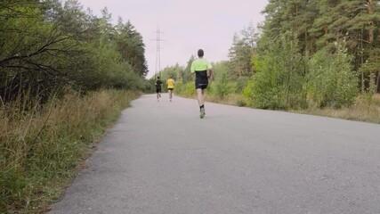 Wall Mural - runners men athletes leaders run marathon in autumn park