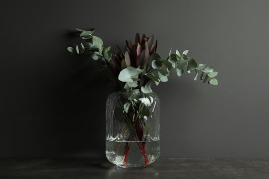Bouquet of protea flowers and eucalyptus branches in glass vase on table against black background