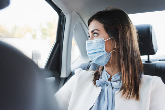 woman in medical mask looking out window while sitting on back seat of car on blurred background