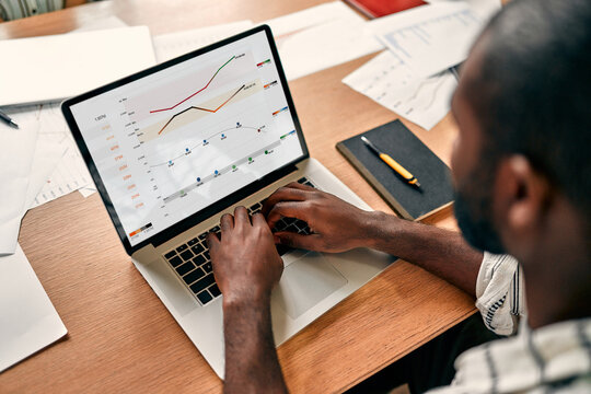 African businessman analyzing statistics on laptop screen, working with financial charts on the internet, using business software for data analysis and project management concept, close-up rear view