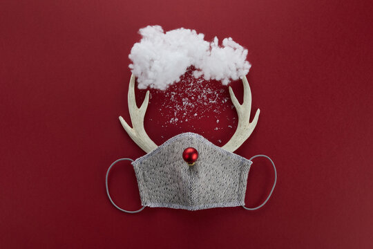 Reindeer horns with face mask and red ball and cloud. Pandemic Christmas concept. Flat lay.