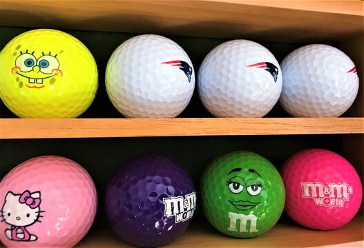 Moscow, Russia, July 2019: Close-up of shelves of wooden rack, which stands on the shelves of eight different Golf balls from the collection, colorful, with different logos