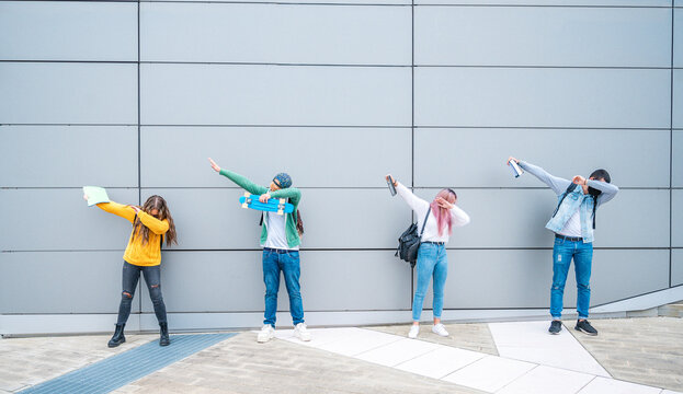Happy multiracial teenage friends in casual clothes dancing dub dance on grey wall background after school.- New normal lifestyle concept with young students having fun together near to the campus