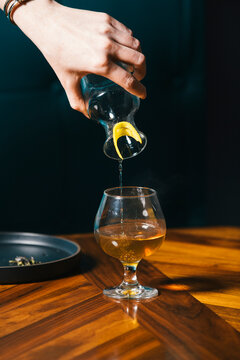 Woman's hand pouring drink in glass on table