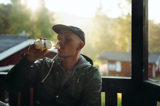 Man having drink while sitting on bench