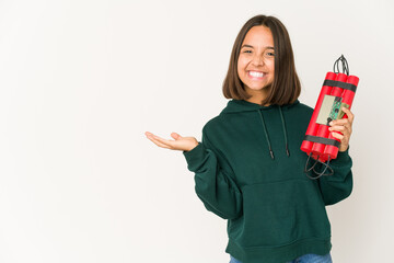Young hispanic woman holding dynamite showing a copy space on a palm and holding another hand on waist.