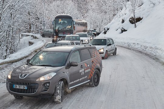 Alpe d'Huez, France - CIRCA 2020: Cars after a blizzard on the amountain road to the ski resort, congestion with line of cars and tourist buses stuck