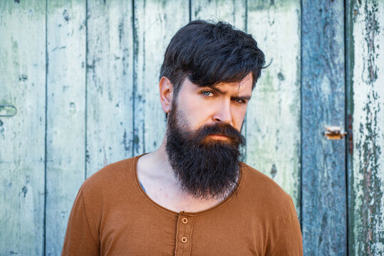 Young handsome man, portrait face of serious bearded hipster on wooden background.