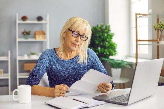 Sad senior lady reading utility bill, bank account balance notification or novel rejection letter