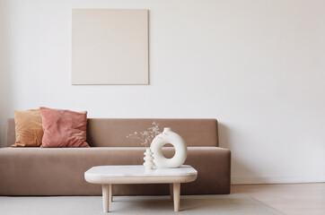 Blank picture frame mockup on white wall. White living room design. View of modern scandinavian style interior with sofa. Home staging and minimalism concept