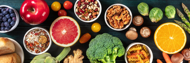 Healthy vegan food panorama. Top shot of fruits and vegetables, legumes, mushrooms, nuts. Balanced diet concept, on a dark background