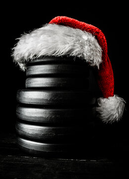 Heavy dumbbells weight plates stacked on top of each other in the shape of a snowman, with red Santa Claus hat. Healthy fitness lifestyle Christmas concept.