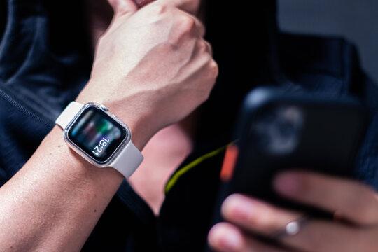 アップルウォッチをつけた手を顎にあててスマホでネットサーフィンする男性の手元クローズアップ。Apple Watch Series 6で時短/効率化/健康管理。テクノロジーと日常