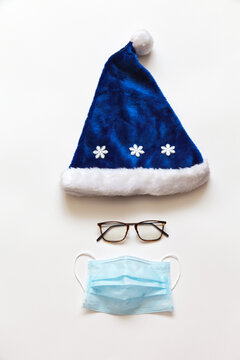 Christmas and New Year holidays in coronavirus pandemic. Blue Santa hat, goggles and a protective medical face mask to protect against the virus. Safe holidays concept. Flat lay, copy space, top view