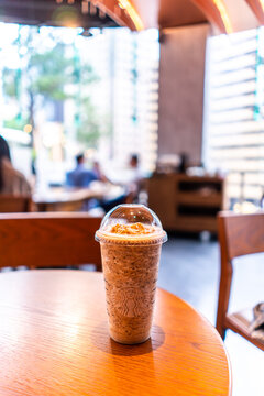 Taipei, Taiwan - October 9, 2020: Glass of Starbuck Coffee Frappuccino Blended Beverages served at wood table in starbuck shop in Taiwan.