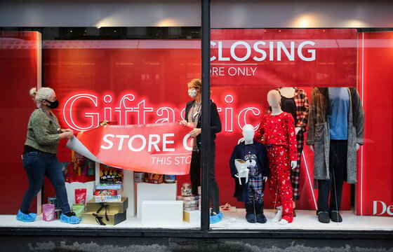Members of staff attach a closing down sign in a window of Debenhams store in Manchester