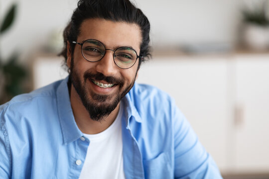 Closeup Portrait Of Positive Indian Guy With Dental Braces And Eyeglasses
