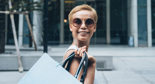 Smiling woman carries a shopping bag over her shoulder in front of shopping mall