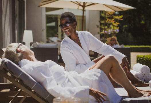 Happy senior women friends relaxing in spa robes on sunny hotel patio