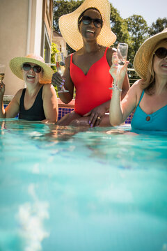 Happy senior women friends drinking champagne in sunny swimming pool