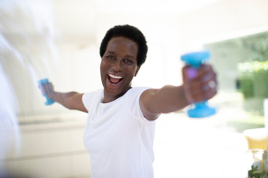 Portrait energetic mature woman exercising with dumbbells at home