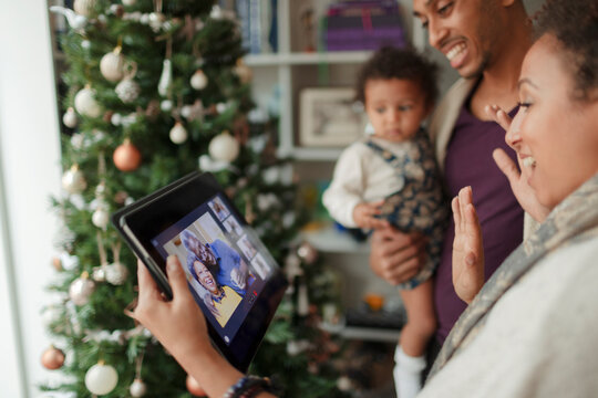 Family video chatting on digital tablet screen at Christmas