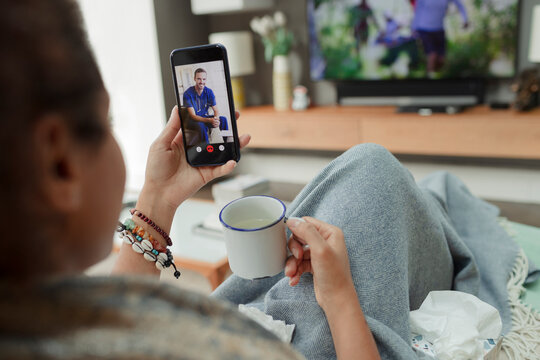 Sick woman video chatting with doctor on smart phone screen at home