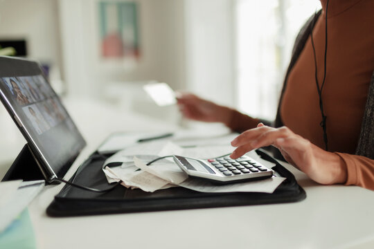 Woman with calculator and receipts paying bills at digital tablet
