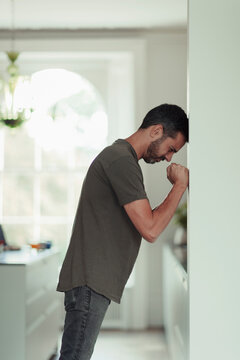 Frustrated man with clenched fists leaning against wall