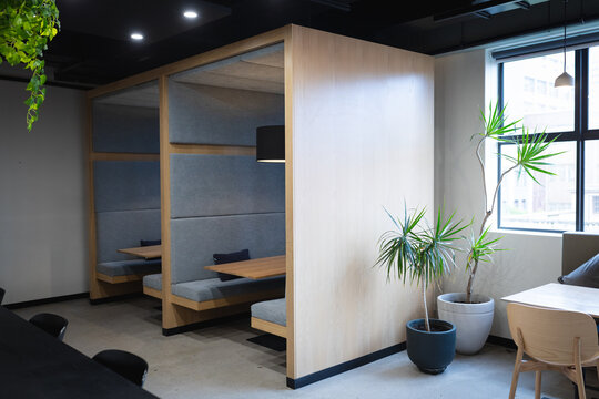Empty cafeteria in creative office with booths, table, window and plants