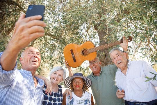 gruppo di anziani amici con la chitarra si fanno un selfie con il cellulare all'ombra di un ulivo