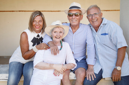 Gruppo di anziani amici che si divertono seduti su un muretto