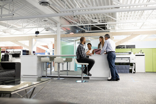 Businesspeople meeting at high bar table in modern office