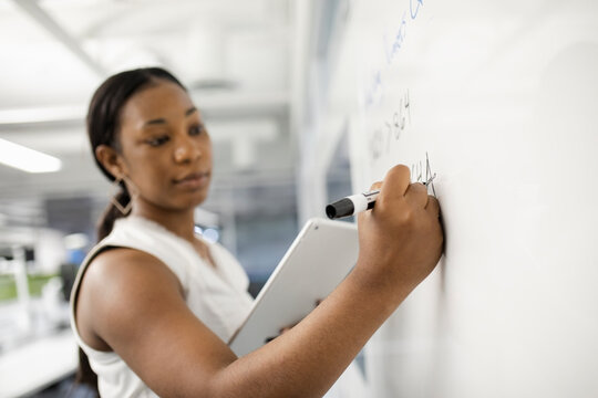 Woman using digital tablet writing on office whiteboard