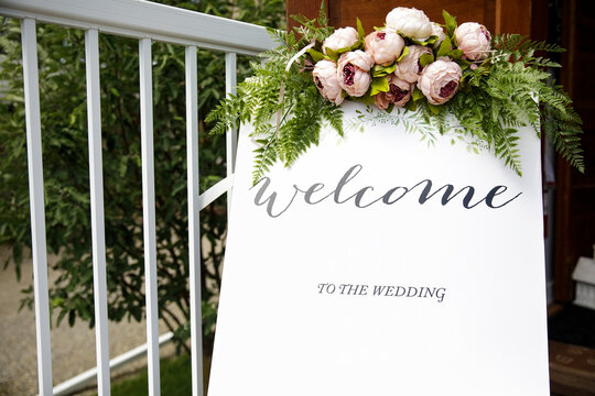 Wedding welcome sign and peony flowers at church entrance