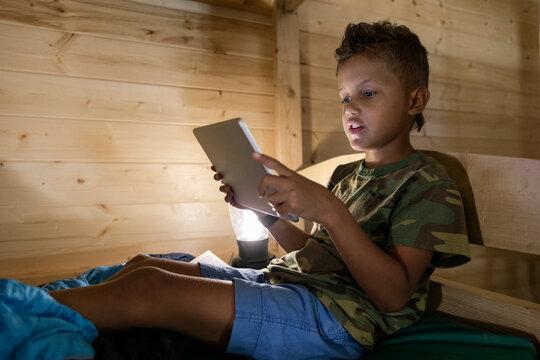 Boy using digital tablet in cabin at summer camp