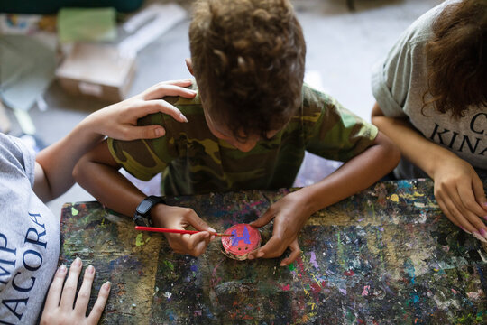 Boy decorating piece of wood in craft activity at summer camp