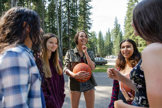 Girls chatting on basketball court at summer camp