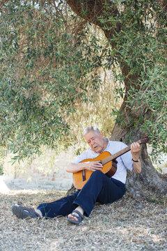 Uomo anziano suona malinconicamente una canzone con la chitarra seduto sotto un ulivo in un parco