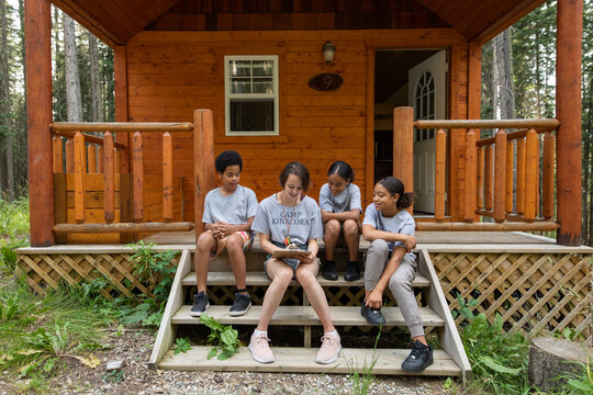 Camp counselor with clipboard sitting with children on steps of cabin