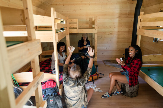 Women playing cards in cabin at summer camp