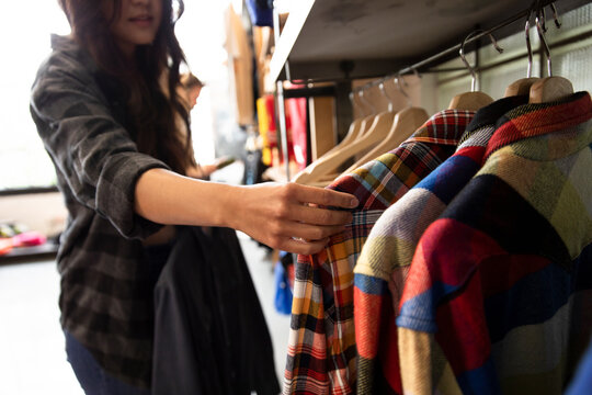 Woman shopping for plaid shirts in clothing store
